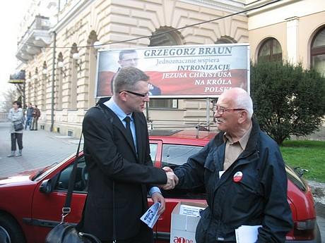 Grzegorz Braun ściska dłoń jednego zeswoich zwolenników - fot.Rajmun Pollak