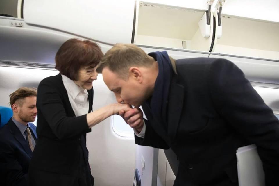 Prezydent RP Andrzej Duda wita pocałunkiem wrękę Zofię Pilecką napokładzie samolotu