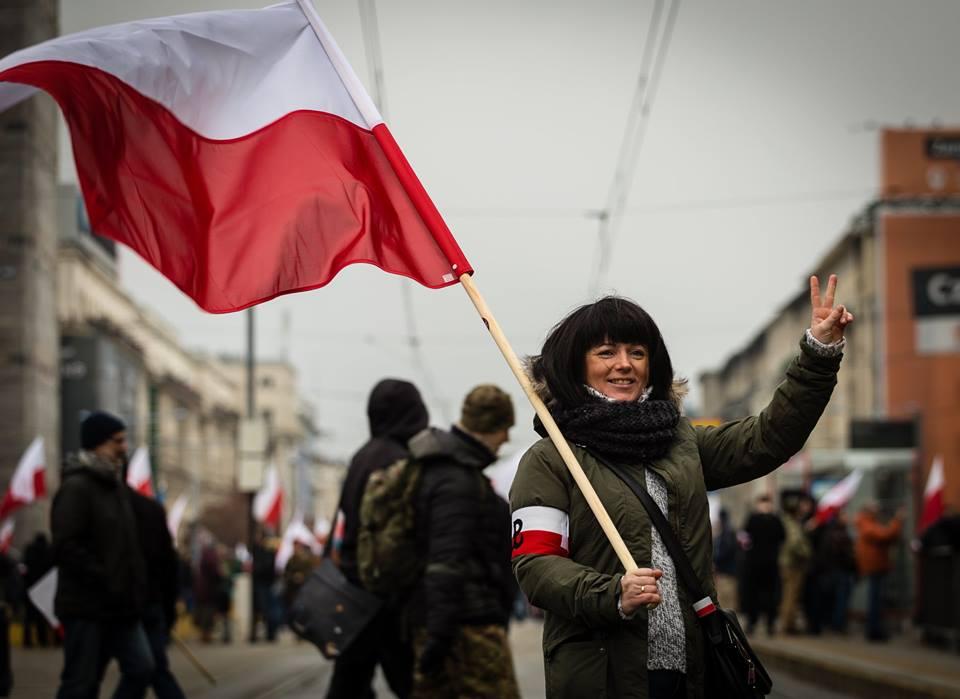 artur-ceyrowski-marsz-niepodleglosci-2016-kobieta-z-bialo-czerwona-flaga-i-znakiem-zwyciestwa